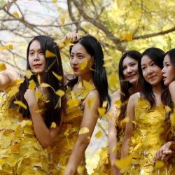 Students Wearing Golden Cloths Made up of Gingko Leaves